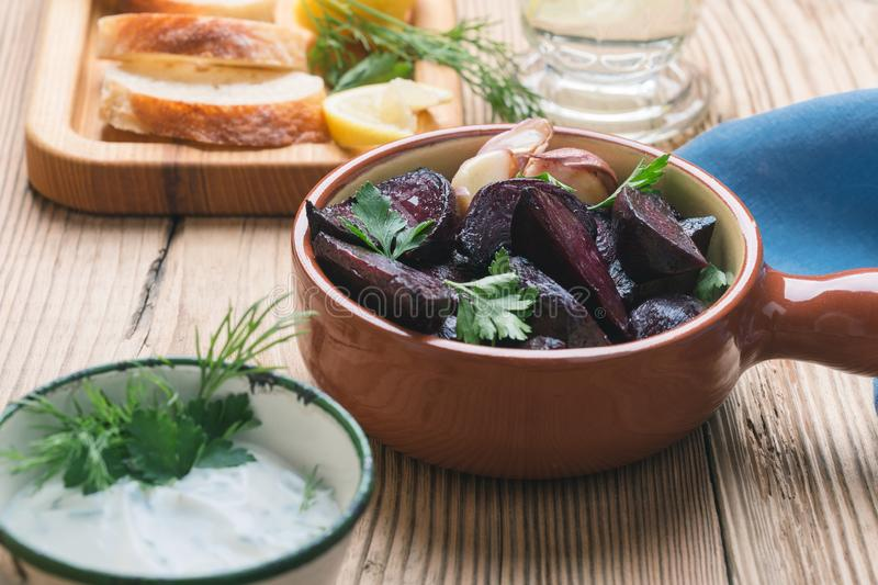 Yogurt dip with parsley, roasted beets, vegan plant based meal. Yogurt dip with parsley, dill and lemon juice served on rustic wooden table with roasted beets stock photo