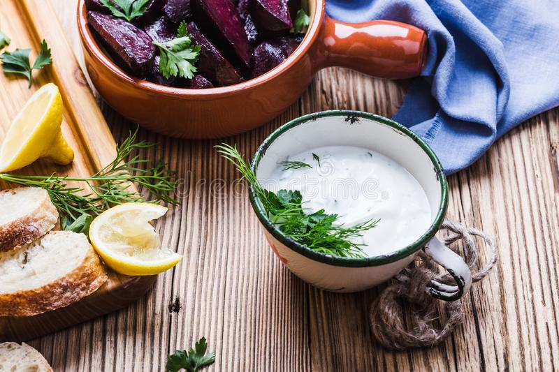 Yogurt dip with parsley, roasted beets, vegan plant based meal. Yogurt dip with parsley, dill and lemon juice served on rustic wooden table with roasted beets royalty free stock image