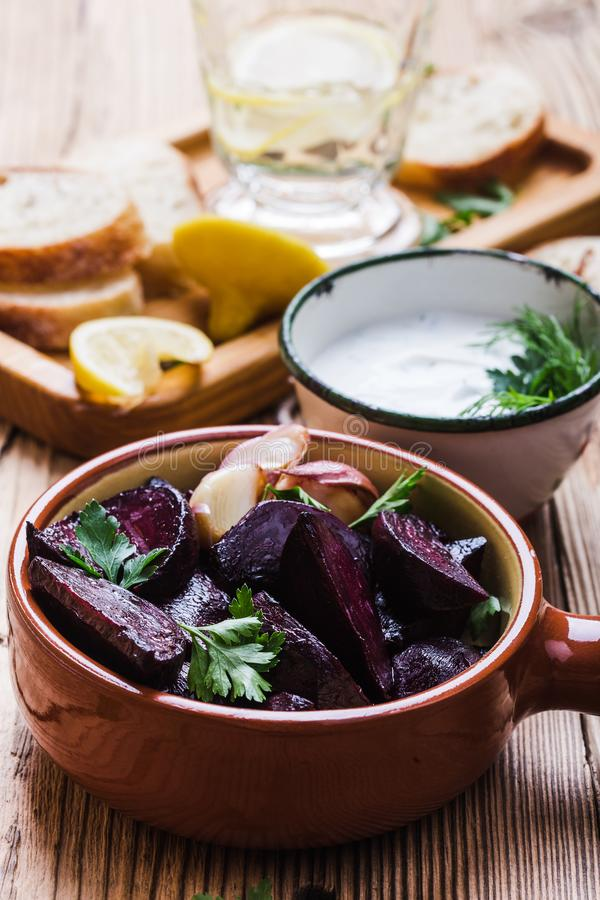 Yogurt dip with parsley, roasted beets, vegan plant based meal. Yogurt dip with parsley, dill and lemon juice served on rustic wooden table with roasted beets stock photos