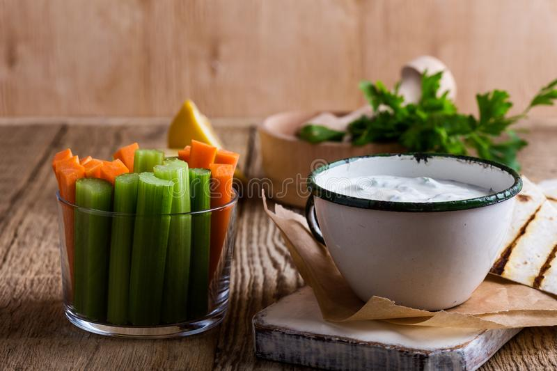 Yogurt dip with parsley  served  with carrot and celery sticks. Yogurt dip with parsley and lemon juice served on rustic wooden table with tortilla chips and royalty free stock photography