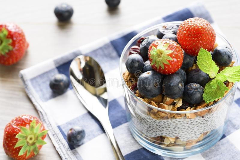 Yogurt with granola, fresh blueberries, chia seeds and oats in a glass over wood background. close up royalty free stock photo