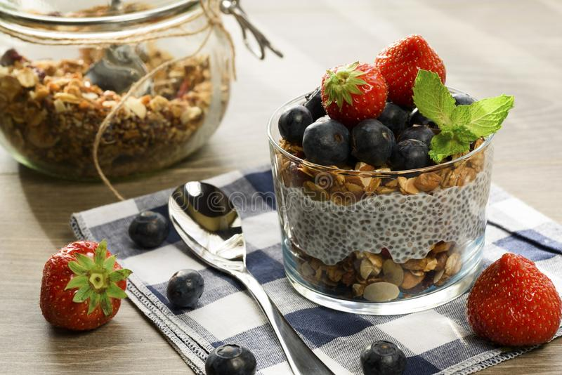 Yogurt with granola, fresh blueberries, chia seeds and oats in a glass over wood background. close up.  stock photos