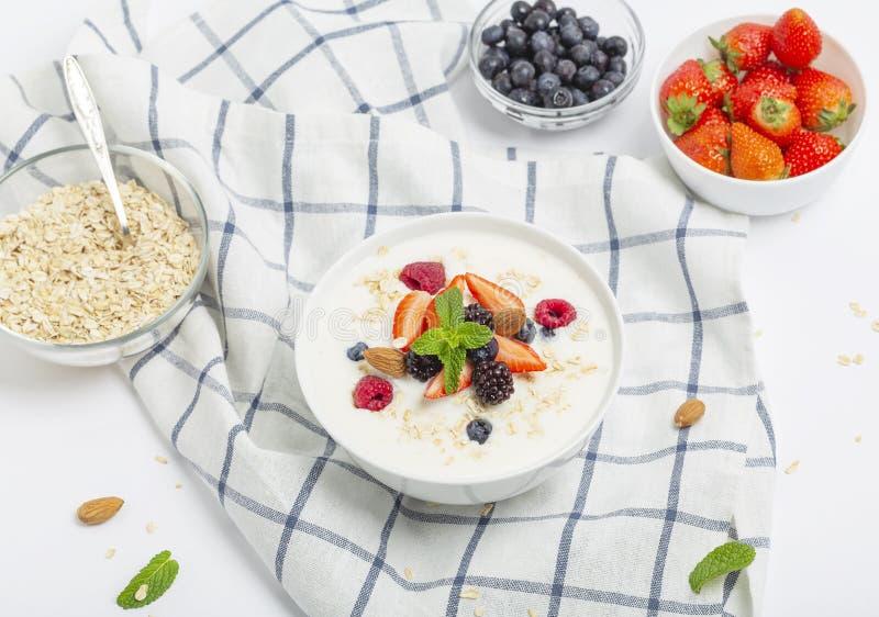 Yogurt with granola, fresh strawberries, raspberry, blueberries, blackberries, almonds and mint. Healthy snack. Breakfast food. Vegan food royalty free stock images
