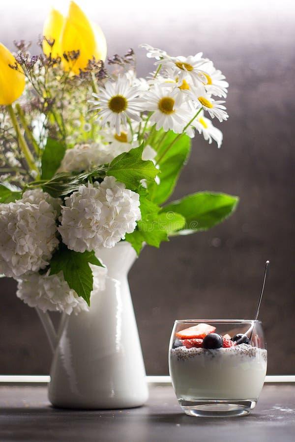 Yogurt greco con i semi di chia della noce di cocco e frutta fresca accanto ai fiori nel vaso fotografie stock