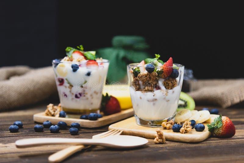 Yogurt greco sano con Granola e le bacche miste sui tum di legno immagini stock libere da diritti