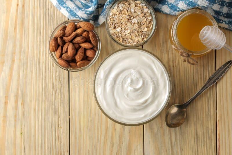 Yogurt greco in una ciotola di vetro accanto al dado della farina d'avena e del miele e della mandorla su un fondo di legno natur fotografia stock libera da diritti