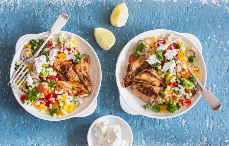 Yogurt marinated grilled chicken breast and israeli couscous and vegetables tabouli salad on a blue background royalty free stock images