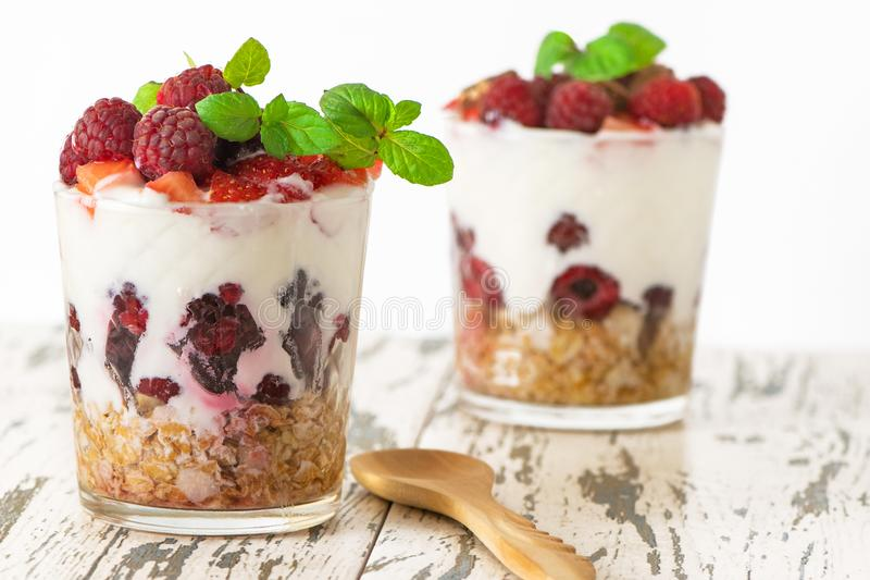 Yogurt with muesli and berries in two glasses on light wooden table royalty free stock image