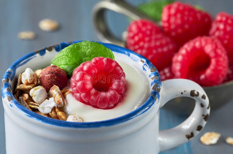 Yogurt with muesli, raspberry and nuts, healthy dessert on light blue background stock images