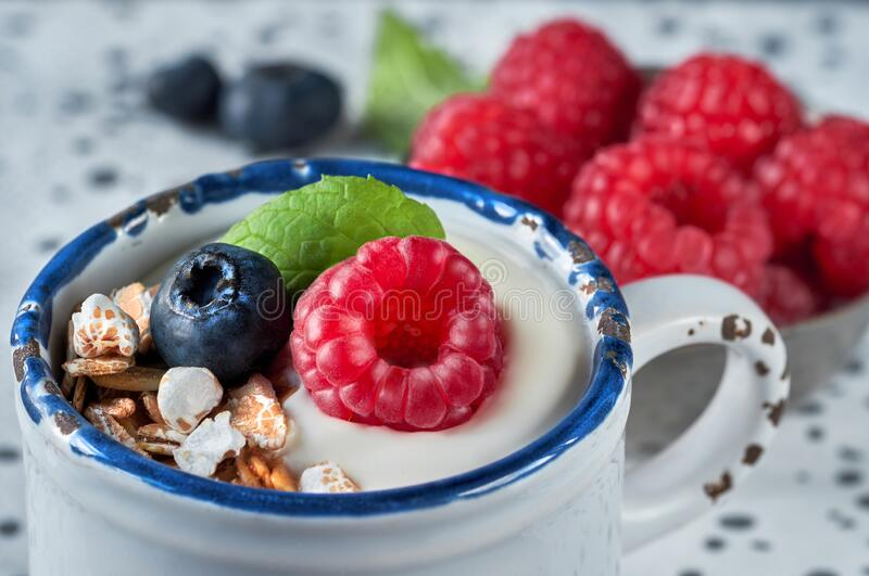 Yogurt with muesli, raspberry and nuts, healthy dessert on light blue wood with more berries on light background stock photography