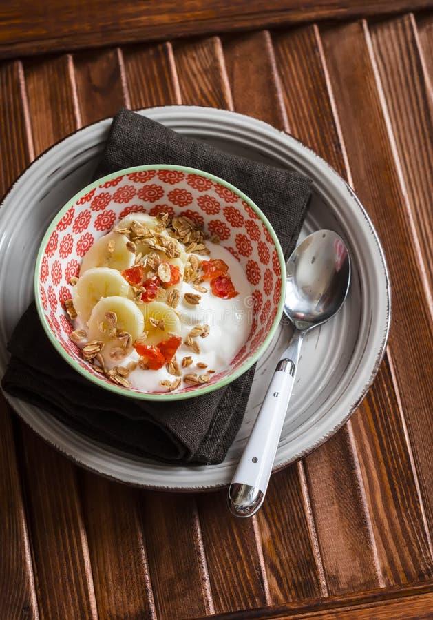 Yogurt naturale con la banana, le albicocche secche ed il granola croccante in una ciotola d'annata fotografie stock libere da diritti