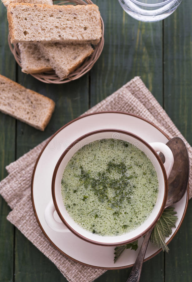 Yogurt and nettle cold soup. On green table stock photography