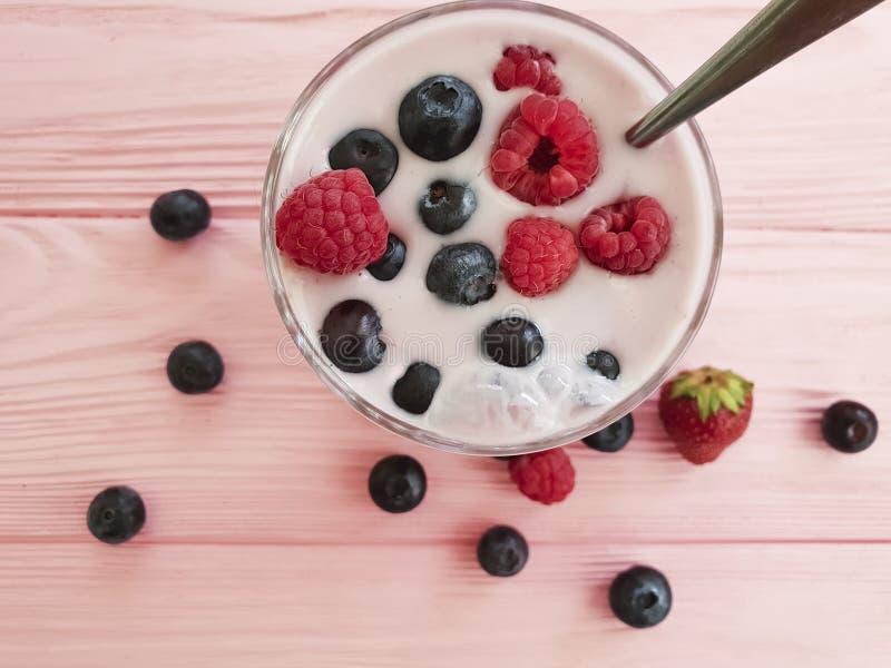 Yogurt, strawberry, raspberry, blueberries homemade a pink wooden background,. Yogurt strawberry raspberry blueberries on a pink wooden background homemade royalty free stock photos