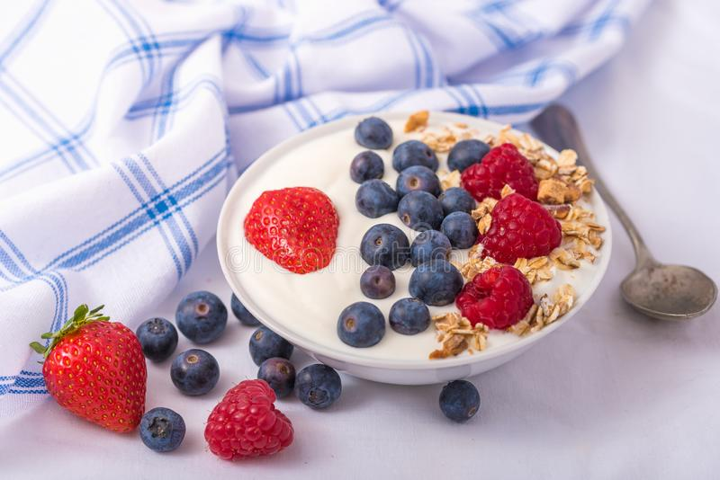 Yogurt in white bowl with strawberries and blueberries on white background stock images