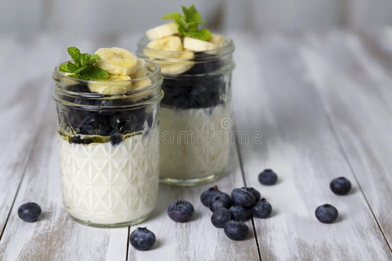 Yogurt wit blueberries & sliced bananas stock images
