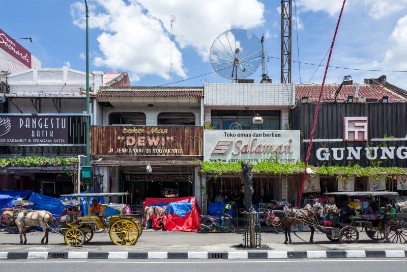 Yogyakarta, Indonésia - os transportes puxados por cavalos esperam clientes na estrada de Malioboro em Yogyakarta imagem de stock