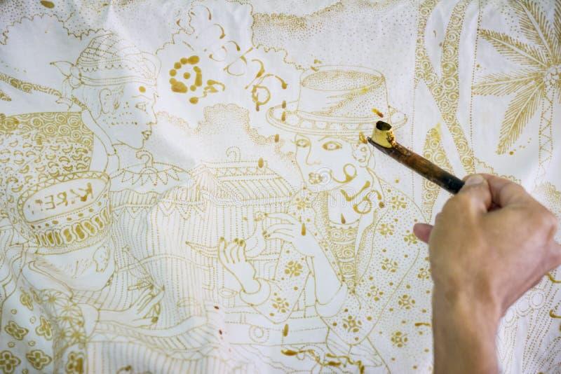 Unknown man making batik on a fabric. Yogyakarta - Indonesia. April 10, 2018: Hand of unknown man making batik on a fabric using a canting and wax in Yogyakarta royalty free stock photos