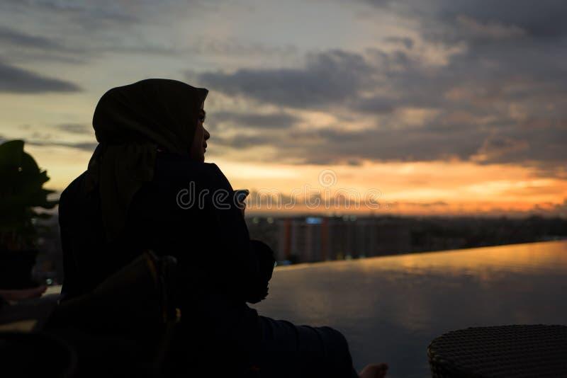 Yogyakarta, Indonesia - 16 de marzo de 2018: Mujer musulmán que disfruta de puesta del sol en la piscina fotografía de archivo libre de regalías