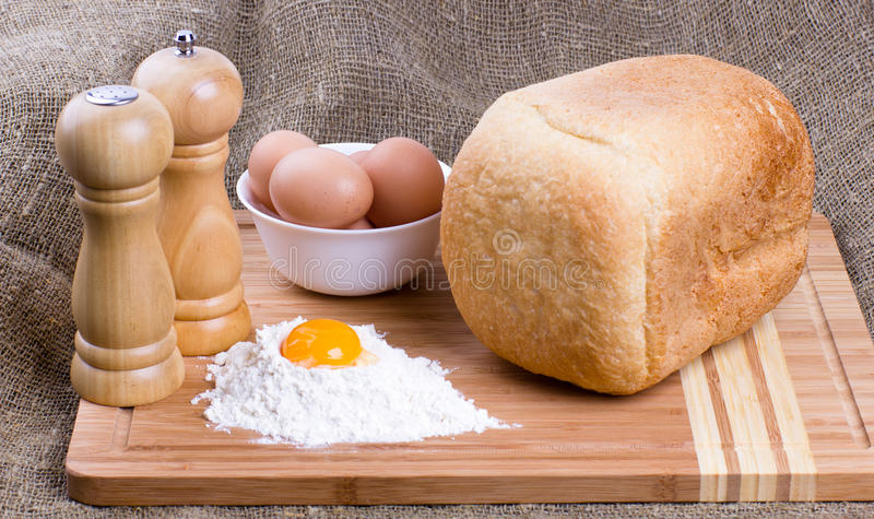 Yolk, eggs of house hens, salt, pepper and bread royalty free stock images