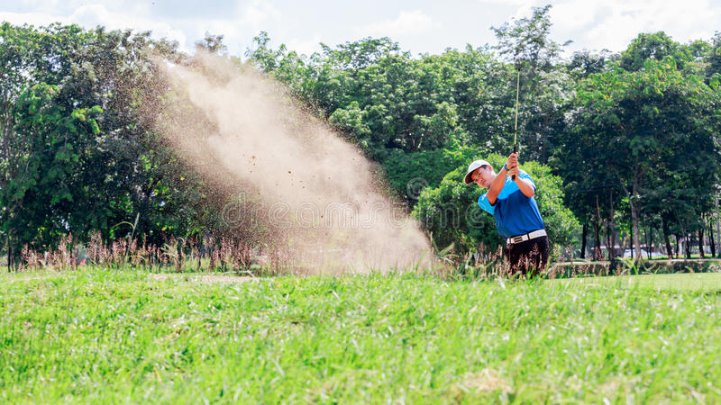 Yong asian golfer explosion sand. stock photography