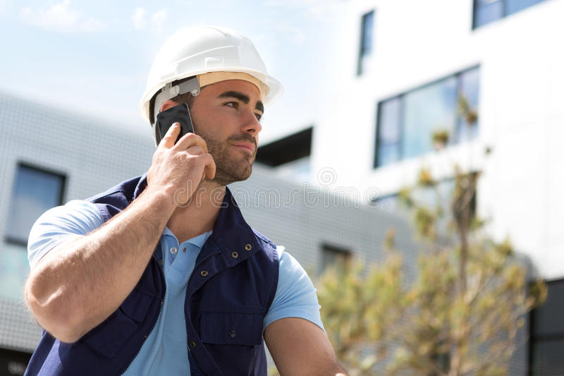 Yong atrakcyjny pracownik używa telefon komórkowego na budowie siedzi zdjęcia stock