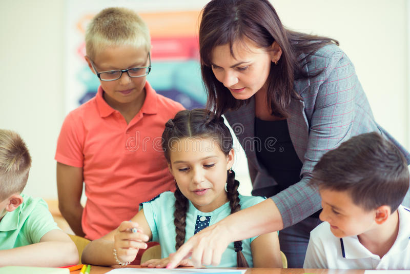Yong beautiful teacher with group of clewer children in school royalty free stock images