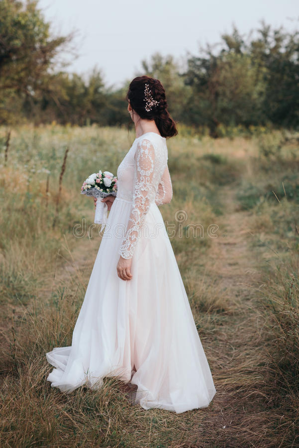 Yong bride spinning in a white dress on the bank on nature. royalty free stock images