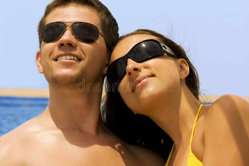Yong couple. Young couple are looking up,it is the sea behind them stock photography