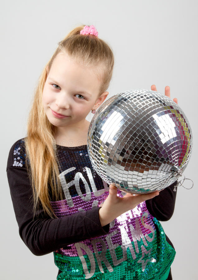 Yong cute blonde girl holding a disco ball royalty free stock images