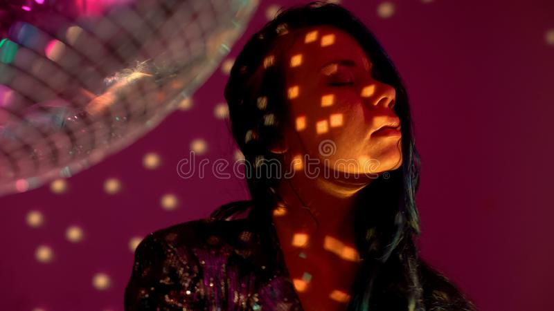 Yong female enjoying party atmosphere in night club, standing by disco ball. Stock photo stock photography