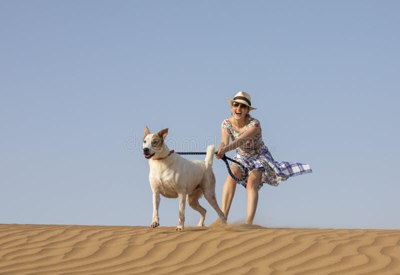 Yong-Frau mit einem Hund in einer Wüste stockfotografie