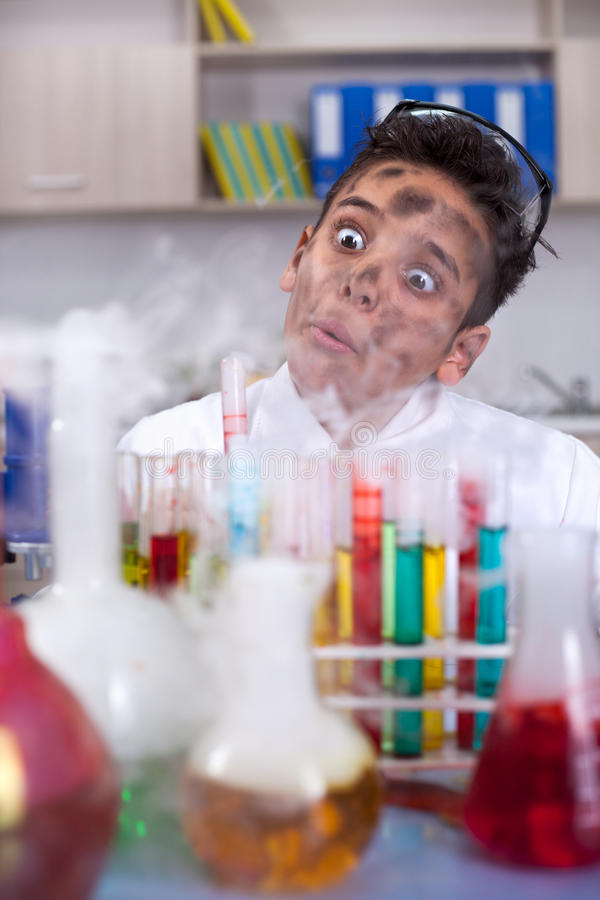 Yong funny scientist doing some crazy experiment. Boy doing experiments in the laboratory,Science and education concept stock photography