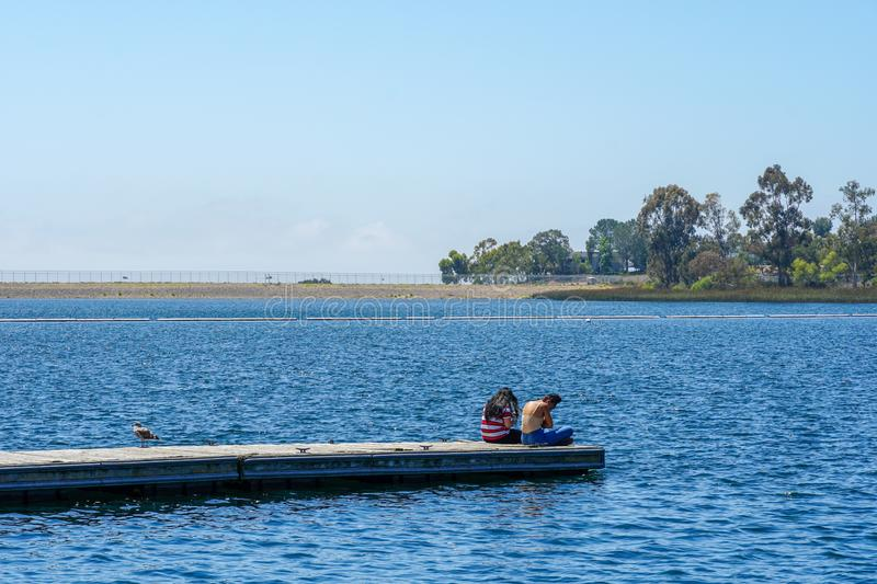Yong girls sitting on the wooden pier and having a relax time. Friends happiness. Yong girls sitting on the wooden pier and having a relax time. Miramare Lake royalty free stock images