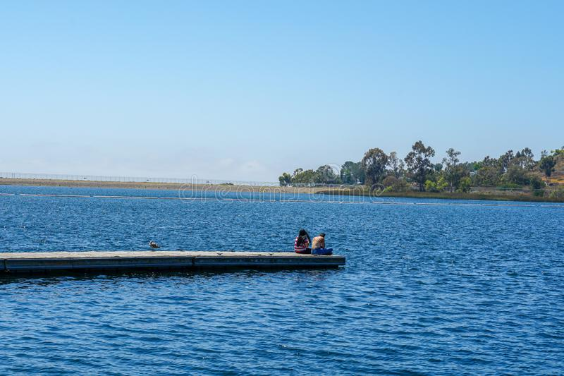 Yong girls sitting on the wooden pier and having a relax time. Friends happiness. Yong girls sitting on the wooden pier and having a relax time. Miramare Lake royalty free stock photos