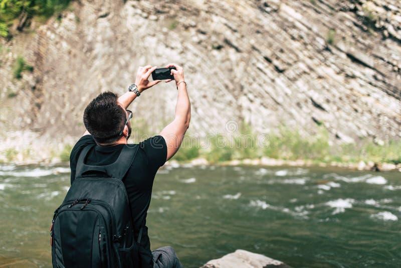 Yong handelsresande som tar fotoet nära bergfloden royaltyfri bild