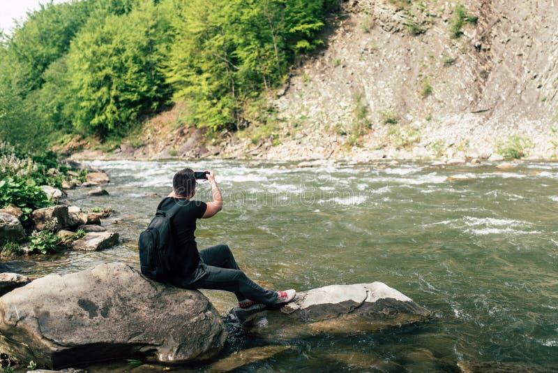 Yong handelsresande som tar fotoet nära bergfloden fotografering för bildbyråer