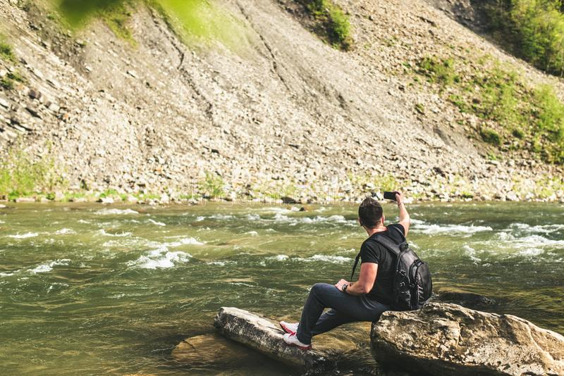 Yong handelsresande som tar fotoet nära bergfloden arkivbild