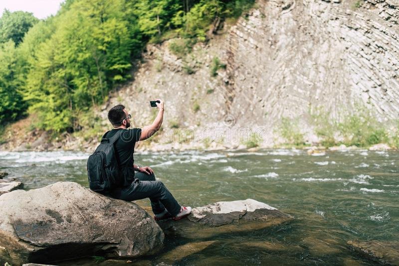 Yong handelsresande som tar fotoet nära bergfloden arkivfoton