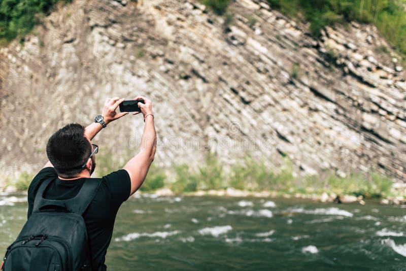 Yong handelsresande som tar fotoet nära bergfloden arkivfoto