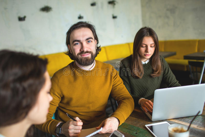 Yong hipster male and females in cafe working with laptop. With coffee on wooden table stock image