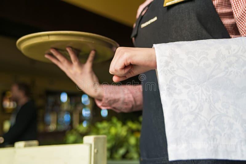 Yong kelner trzyma tacę i pieluchę zdjęcia royalty free