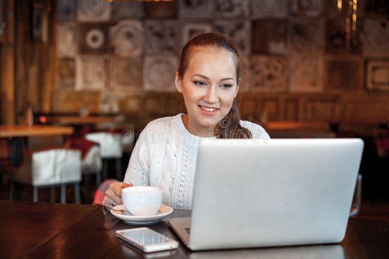 Yong kvinna ett arbete på bärbara datorn i kafé royaltyfri fotografi
