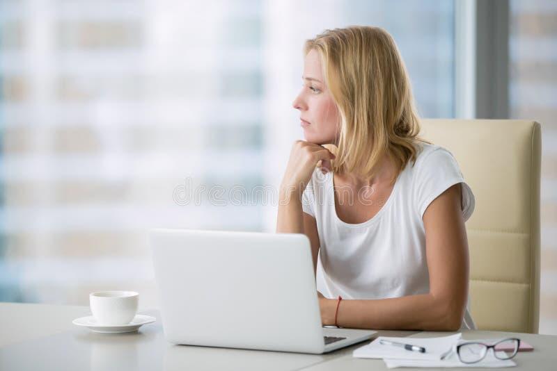 Yong kvinna med bärbara datorn som ser fönstret arkivbild