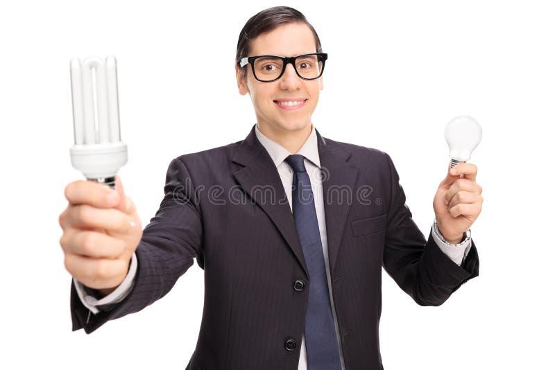 Yong mężczyzna trzyma dwa żarówki w czarnym kostiumu obrazy royalty free