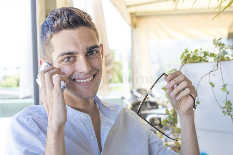Yong man with cellphone. In the summer day stock image