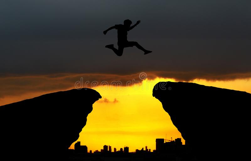 Yong man jump over city scaoe and through on the gap of hill silhouette evening colorful sky. Image for spirit and brave concept.man is representative of royalty free stock photo