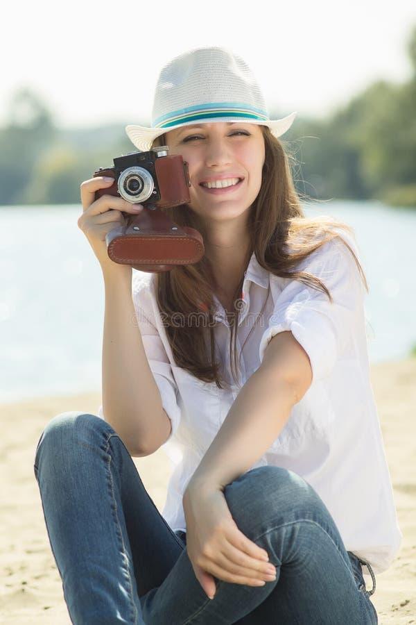Yong modnisia dziewczyny strzelanina z starą kamerą przy plażą zdjęcia royalty free