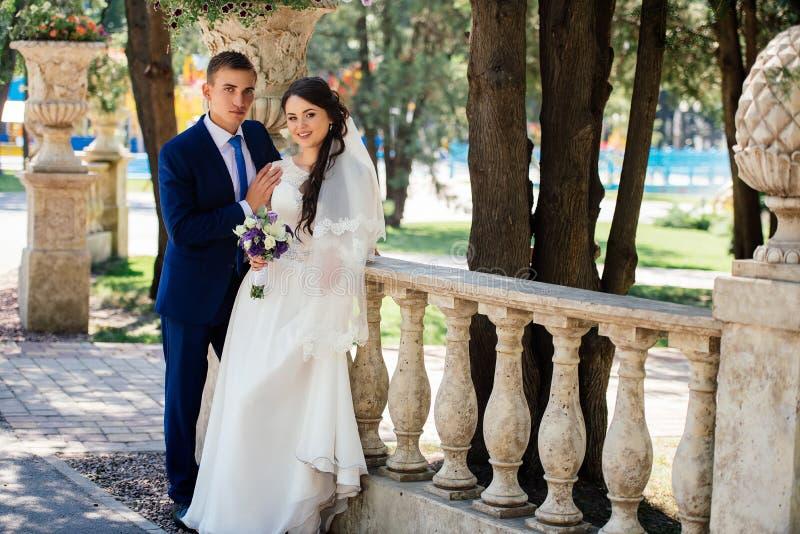 Yong państwa młodzi piękni uściśnięcia outdoors panna młoda obejmuje fornala Ślubna para w miłości przy wedd dniem fotografia stock
