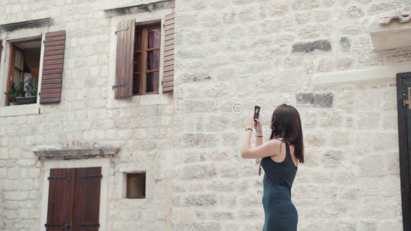 Yong Woman Taking Pictures By Smartphone Donna alla moda del viaggiatore di estate con il telefono all'aperto in città europea, C immagini stock