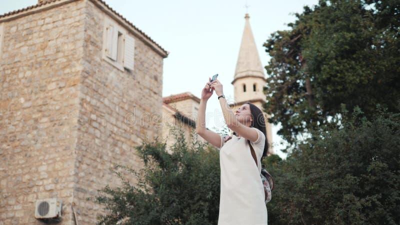Yong Woman Taking Pictures By Smartphone Mulher à moda do viajante do verão com telefone fora na cidade europeia, cidade velha imagens de stock